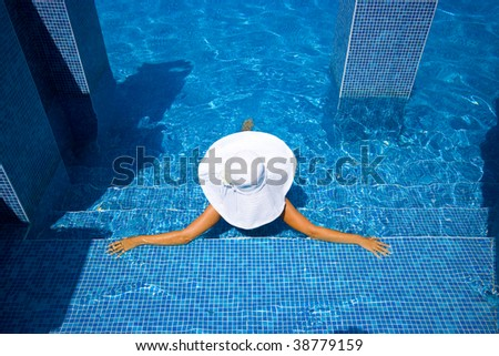 Girl in white hat sitting in the swimming pool