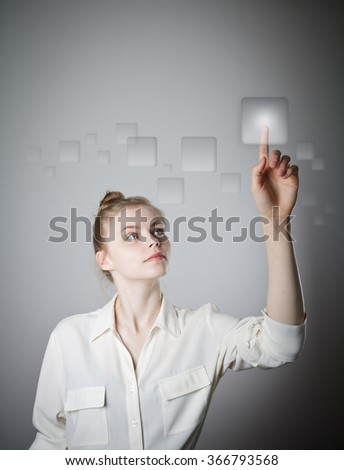 Girl in white is pushing the virtual button. Young slim woman. - stock photo