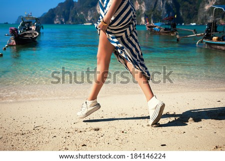 Girl in white leather boots and long dress jumping and have fun at beautiful beach at thailand. - stock photo