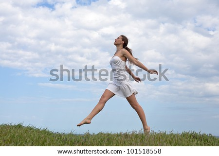 Girl in white on open air. Attractive young woman in white dress running along field - stock photo