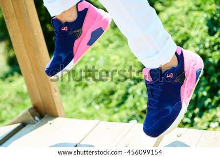 Girl in white pants wearing fashion sport shoes, blue and pink, on a sunny day - stock photo