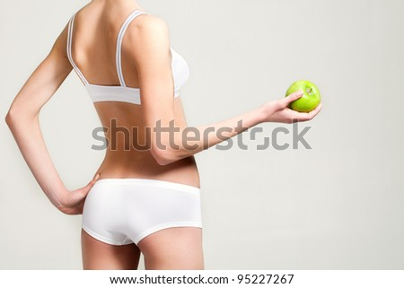 girl in white underwear with a green apple in a cookie - stock photo