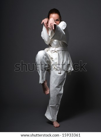 Girl in white uniform stands against the dark background, special pose of aikido