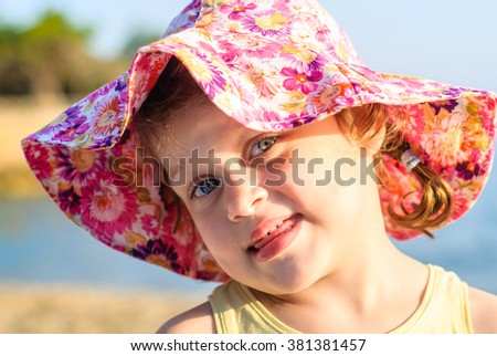 Girl in wide-brimmed hat looking into the camera and bit her tongue on the beach
