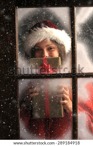Girl in window covered with frost holding a Christmas Present in front of her face vertical composition. Outside it is snowing.