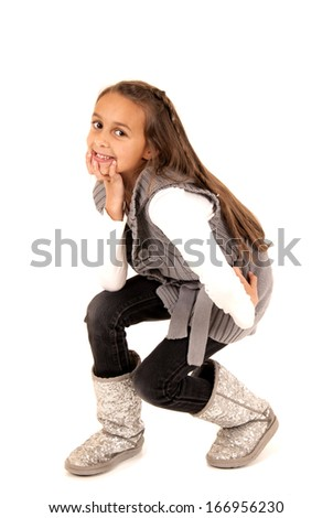 girl in winter boots squatting down smiling