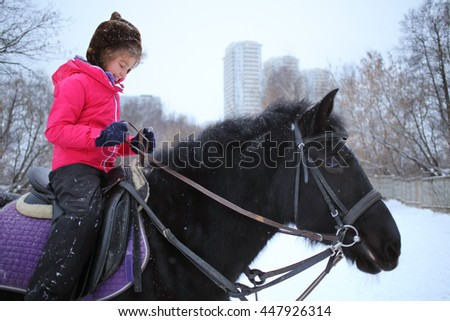 Girl in winter clothes on a black horse at the equestrian site in front of trees and buildings - stock photo