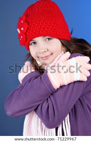 Girl in winter clothes on blue background - stock photo