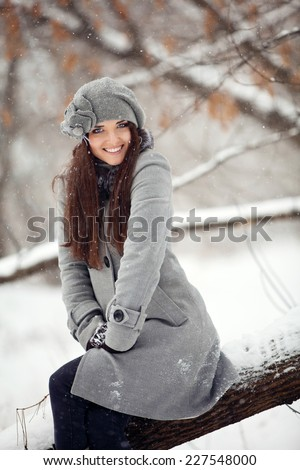 Girl in winter forest sitting on timber - stock photo
