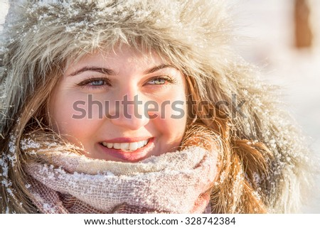 Girl in winter park. Girl smiling, portrait. Girl dressed in a fur hat and warm gloves. - stock photo