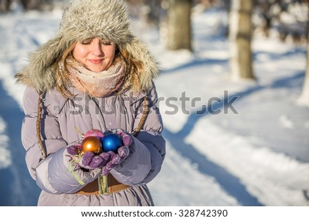 Girl in winter park. The girl is holding a Christmas balls, ulybaetsya. Girl wearing a fur hat and warm gloves. - stock photo