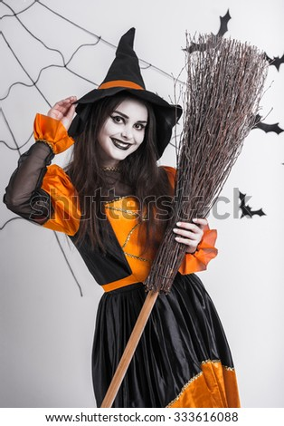 Girl in witch clothing, Halloween celebration, on the background of bats and cobwebs