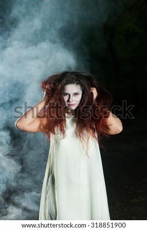 Girl in witch costume for Halloween in a forest. Beautiful zombie bride in halloween. Zombie girl.