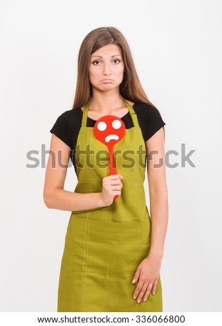 Girl in yellow apron with a sad face spatula - stock photo