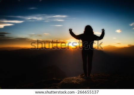 Girl in yoga meditation on top of a mountain at sunset
