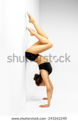 girl in yoga pose on a gray background