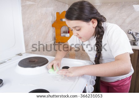 Girl intently cleans plate and peers