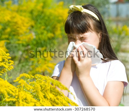 Girl is blowing her nose, allergic to bloom flowers - stock photo