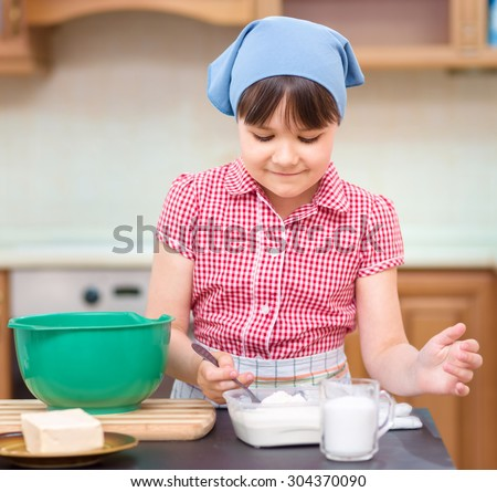 Girl is cooking, adding a spoon of sugar to bowl, indoor shoot - stock photo