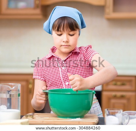 Girl is cooking, mixing something bowl, indoor shoot - stock photo