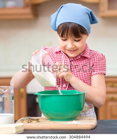 Girl is cooking, pouring milk in bowl, indoor shoot - stock photo