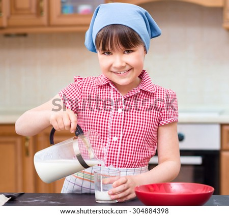 Girl is cooking, pouring milk in glass, indoor shoot - stock photo