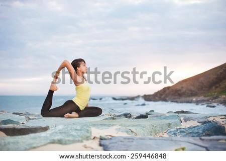 girl is doing yoga, sitting in One-Legged King Pigeon pose (Eka Pada Rajakapotasana ) on rocky beach - stock photo