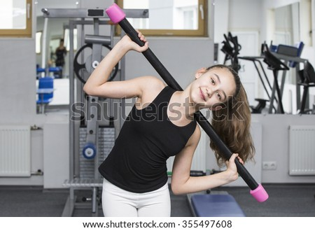 Girl is engaged in sports and gymnastics in the gym
