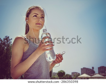 Girl is engaged in sports while listening to music. She is resting and drinking water. - stock photo