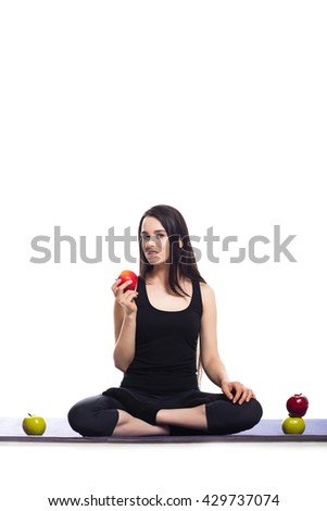 Girl is engaged in yoga on a white background, concept of healthy lifestyle, healthy eating and sport, apples - stock photo