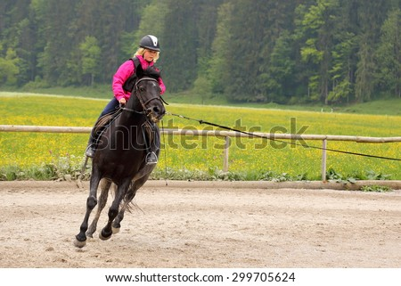 girl is fast riding on a black pony - stock photo