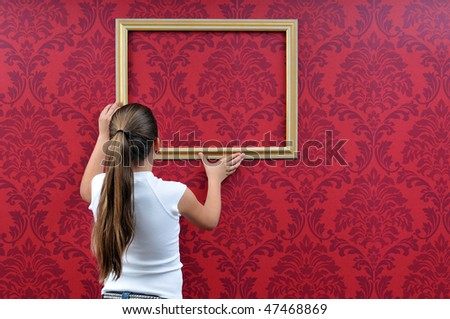 girl is hanging up a picture frame