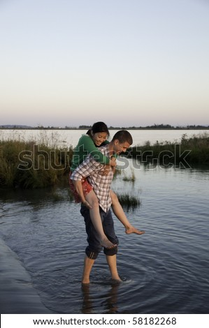 Girl is having a piggy back ride from her boyfriend. - stock photo