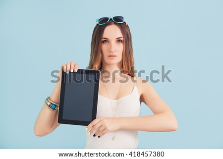 Girl is holding a tablet in hands with screen forward.