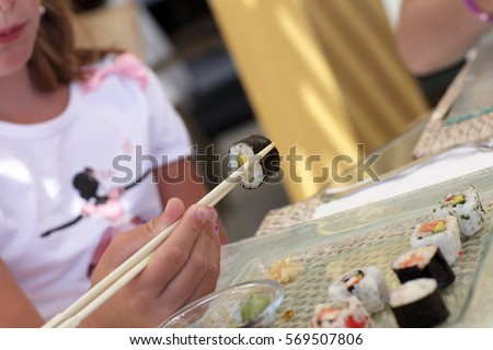Girl is holding futomaki by chopsticks in a japanese restaurant