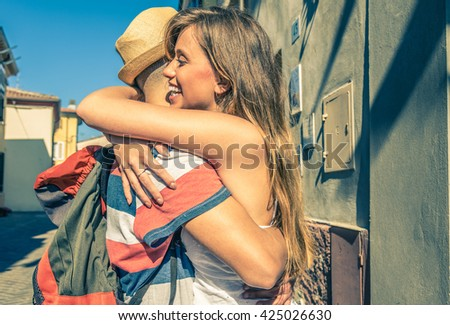 Girl is hugging her boyfriend just back from his trip - caucasian people - urban scene - stock photo