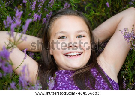 Girl is laying in heather flowers, outdoor shoot