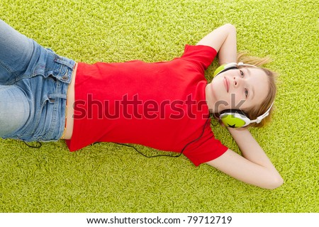 girl is listening to music with headphones on green matt