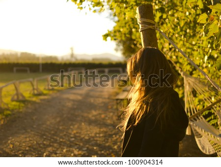 Girl is looking at the horizon with a beautiful sunlight - stock photo