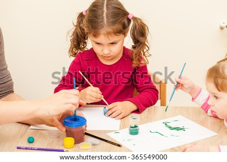 Girl is painting with a brush and watercolors on paper in the kindergarten