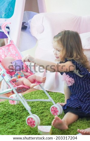 Girl is playing with her doll pretending feeding - stock photo