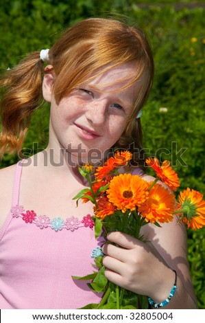 Girl is plucking a bouquet of marigolds in the garden - stock photo