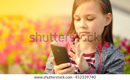 Girl is reading something on a phone - stock photo
