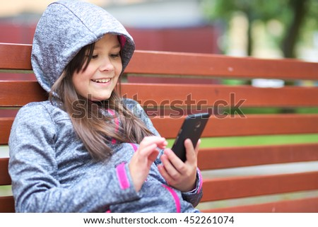 Girl is reading something on phone - stock photo