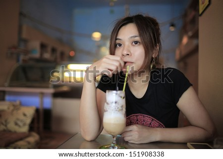 girl is relax to drink the milk coffee, she take her time in the tea time in summer - stock photo