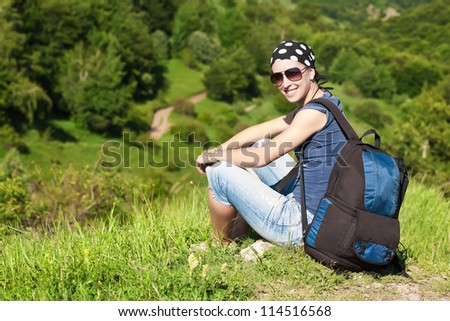 girl is resting sitting on the grass in mountains