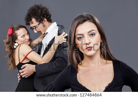 girl is sadly looking while her boyfriend flirts with another woman - stock photo