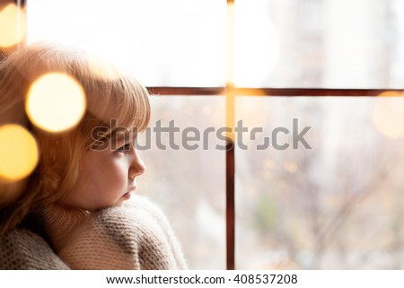 girl is sitting near the window with christmas decorating