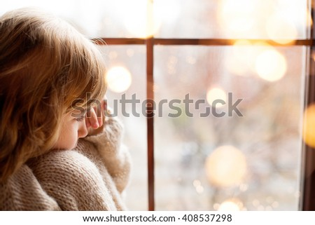 girl is sitting near the window with christmas decorating - stock photo