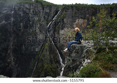 Girl is sitting on the stone above famous Norwegian waterfall Voringfossen - stock photo